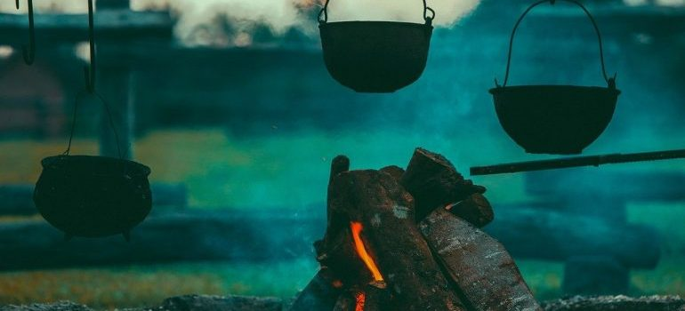 A campfire with pots and pans over an open fire.