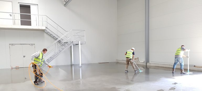 Three men cleaning a warehouse.