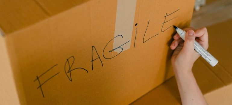 a person writing the word fragile on a cardboard box
