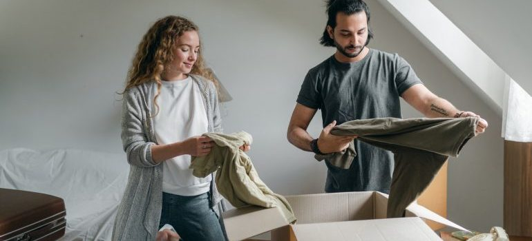 Couple packing clothes in a box