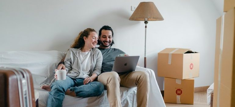 Couple sitting on sofa and readin on their laptop about the risks of doing a last minute move
