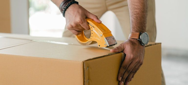 Person following one of the essential tips for long-term storage and packing their belongings in a sturdy box.