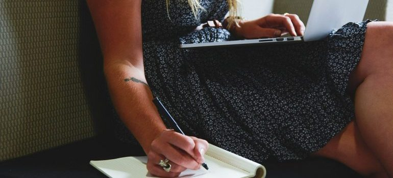 A woman typing on a laptop and writing in a notebook simultaneously.