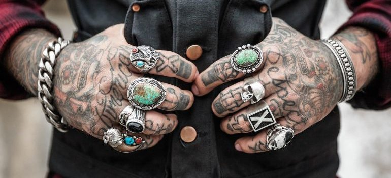 A person with tattoos and rings.