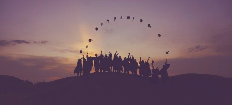 A group of graduates throwing their graduation hats.
