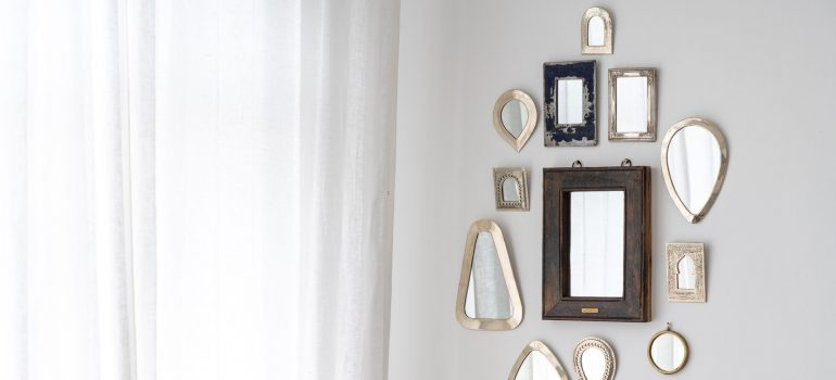 Small mirrors on the white wall.