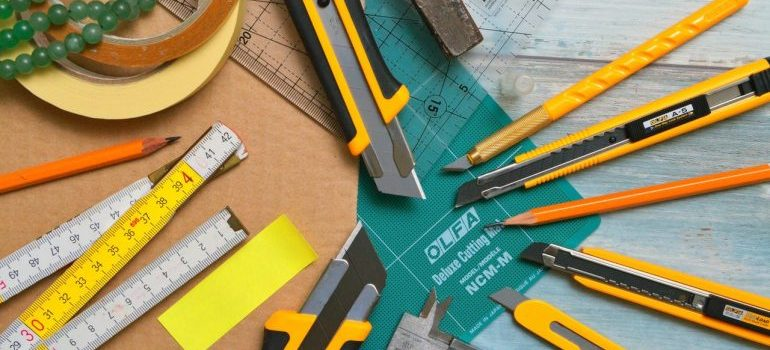 Pens, scalpels, and rulers on a wooden surface.