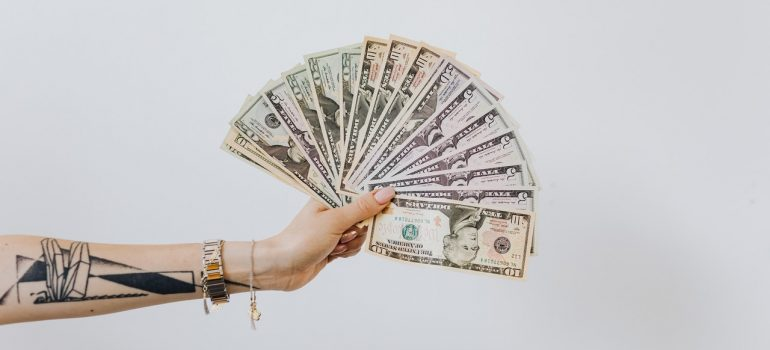 A hand with a tatoo holding a fan of dollar banknotes.