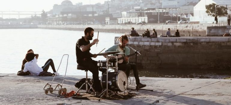 Two guys playing on the pier before storing musical instruments safely