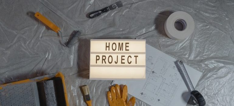 DIY tools on plastic wrapping next to a 'home project' sign, representing storing your work tools long-term.