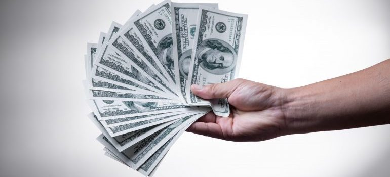 A hand holding dollar bills - why sporting goods stores need self-storage