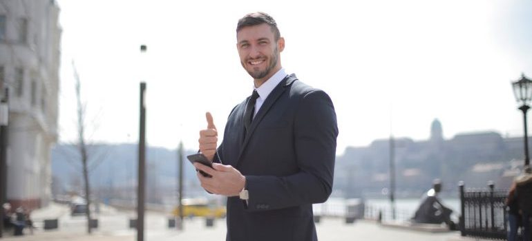 A smiling businessman holding thumbs up, while looking up how self storage saves you money when moving interstate on the phone
