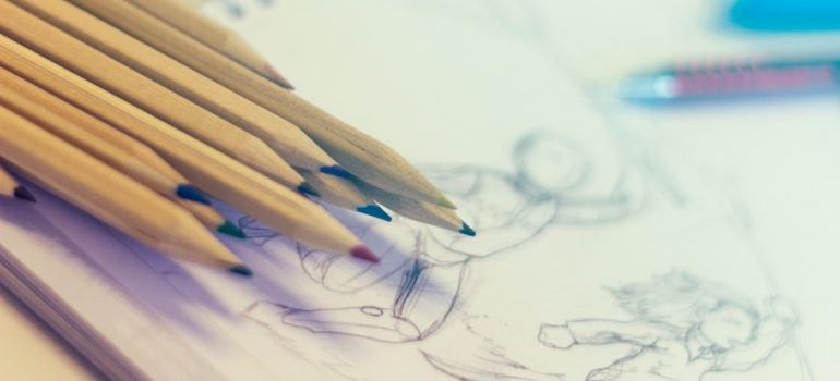 Several pencils resting on a sketch
