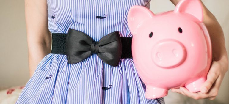 A woman in stripped dress holding a pink piggy bank.