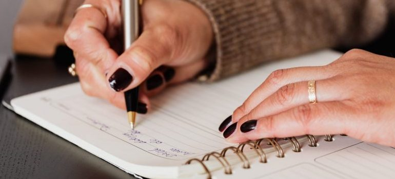 person writing down something in a notebook